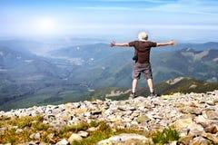 Wanderer mit der Kamera, die in den Bergen steht und das Konkurrierung genießt Lizenzfreies Stockbild