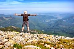 Wanderer mit der Kamera, die in den Bergen steht und das Konkurrierung genießt Stockfotos