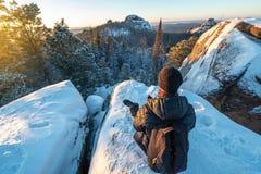 Wanderer mit einem Rucksack, der auf eine Klippe in den Wäldern von Sibirien bei Sonnenuntergang sitzt Schönes Schneepanorama von lizenzfreie stockfotos