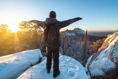 Wanderer mit einem Rucksack steht auf eine Klippe in den Wäldern von Sibirien bei Sonnenuntergang Freiheits- und Wintertrekking stockfoto