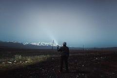 Wanderer mit einem Scheinwerfer unter dem nächtlichen Himmel Stockbild