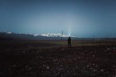 Wanderer mit einem Scheinwerfer unter dem nächtlichen Himmel Stockfoto