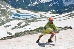 Wanderer mit Eisaxt auf Schnee. Lizenzfreies Stockfoto