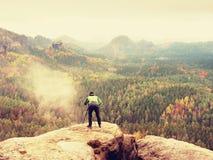 Wanderer mit Kamera auf Stativ macht Foto vom felsigen Gipfel Alleinphotograph an der Randphotographielandschaft Stockfotos