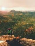 Wanderer mit Kamera auf Stativ macht Foto vom felsigen Gipfel Alleinphotograph an der Randphotographielandschaft Stockfoto