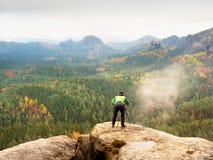 Wanderer mit Kamera auf Stativ macht Foto vom felsigen Gipfel Alleinphotograph an der Randphotographielandschaft Lizenzfreie Stockfotografie