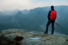 Wanderer mit rotem Rucksack auf scharfem Sandsteinfelsen in den Felsenreichen parken und aufpassend über das nebelhafte und nebel Stockfotos