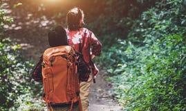 Wanderer mit Rucks?cken gehend durch eine Wiese mit ?ppigem Gras Junger asiatischer weiblicher Hippie zwei, der am Gebirgsfeierta stockfotografie