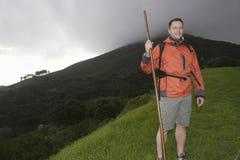 Wanderer mit Spazierstock auf Abhang Lizenzfreie Stockbilder