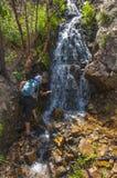 Wanderer nahe dem Wasserfall Stockbilder