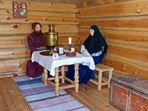 The wanderer old believer and skitnica at the table drinking tea. At the inn. Museum-reserve of wooden architecture and folk art Nizhnyaya Sinyachikha, Russia royalty free stock photography