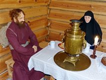 The wanderer old believer and skitnica at the table drinking tea. At the inn. Museum-reserve of wooden architecture and folk art Nizhnyaya Sinyachikha, Russia royalty free stock photo