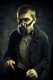 Wanderer of post apocalyptic world. Miserable post apocalyptic wanderer in gas mask over dark grunge background stock photos