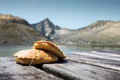 Wanderer ` Sandwich auf einem Holztisch am Fuß von Adamello-Berg Stockfotos