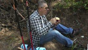 Wanderer schneidet und isst Apfel stock video footage