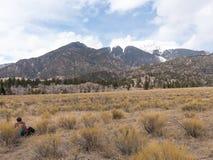 Wanderer sitzt und starrt entlang der Berge entlang der großen Sanddünen Nati an stockfotos