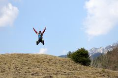 Wanderer springt auf einen Hügel lizenzfreie stockfotografie