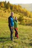 Wanderer stehen in den Herbstbergen still Glückliches Paar sind Lizenzfreies Stockfoto