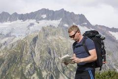 Wanderer sucht nach dem richtigen Weg mithilfe einer Karte Lizenzfreie Stockfotografie