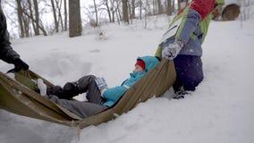 Wanderer tragen Frau mit dem gebrochenen Bein auf palanquin im Wald und treten über Schneewehen stock video footage