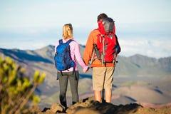 Wanderer, welche die Ansicht von der Gebirgsspitze genießen stockbild