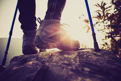 Wandererbeine der jungen Frau, die an der Bergspitze klettern Lizenzfreies Stockbild
