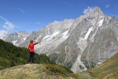 Wandererfrau, die das großartige Jorasses zeigt stockbilder