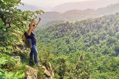 Wandererfrau, die ihre Arme oben auf der hohen Klippe anhebt Lizenzfreies Stockbild