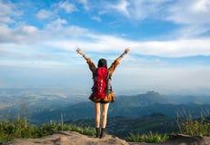 Wandererfrau, die siegreicher Einfassung auf dem Berg glaubt Lizenzfreies Stockbild