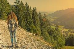 Wandererfrau, die vor schöner Landschaft geht Stockbilder