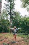 Wandererfrau mit dem Rucksack, der ihre Arme anhebt Stockfoto