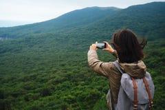 Wandererfrau, welche Fotografien die Landschaft des Berges nimmt Stockfotos
