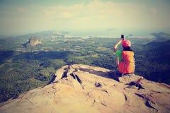 Wanderergebrauch Smartphone, der Foto auf die Küstengebirgsoberseite macht Stockfotos