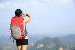 Wanderergebrauchsdigitalkamera, die Foto an der Bergspitzeklippe macht Lizenzfreie Stockfotos