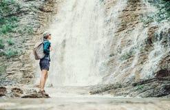 Wanderermädchen, das Ansicht des Wasserfalls genießt Lizenzfreie Stockfotografie