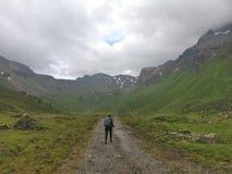 Wanderermädchen, das auf ein Stein- und Schneefeld in den Bergen mit Rucksack geht stockfoto