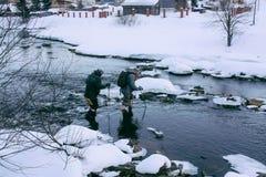 Wanderermann, der den Fluss im Freien im Winter kreuzt Lizenzfreies Stockbild