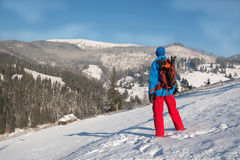 Wanderermann, der in den Winterbergen, stehend auf einem schneebedeckten stillsteht Stockfotografie