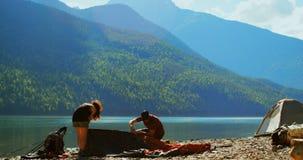 Wandererpaare, die Zelt nahe Flussufer 4k vorbereiten stock footage