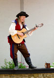 Wandering Bard. A performer stands on a ledge, while entertaining a crowd with an acoustic guitar at a Renaissance Festival Royalty Free Stock Photography