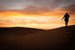 Wandering in the desert. Sunset in the desert with a black silhouette of a person hiking Stock Photography
