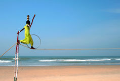 Wandering indian tightrope walker playing on the beach of Goa Royalty Free Stock Photos