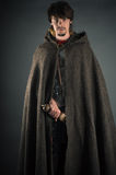 Wandering man in woolen cape with a sword Royalty Free Stock Image