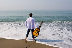 Wandering musician. The young guy (musician) walks on a beach with a guitar royalty free stock photography