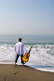 Wandering musician. The young guy (musician) walks on a beach with a guitar stock photos