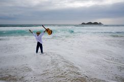 Wandering musician. Storm on the sea. The guitarist stands on coast and and waves hands stock photo