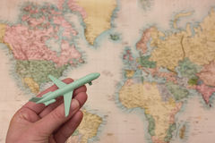 Wanderlust concept - airplane and world map. Wanderlust concept with hand holding airplane and blurred map background Royalty Free Stock Photo
