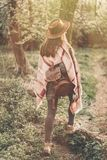 Wanderlust concept. stylish hipster girl in hat with backpack wa. Lking in woods in evening sunshine. woman traveler back view in sunlight among trees. space for Royalty Free Stock Image