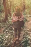 Wanderlust concept. stylish hipster girl in hat with backpack wa. Lking in woods in evening sunshine. bohemian woman traveler exploring in sunlight. space for Royalty Free Stock Photos