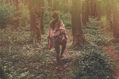 Wanderlust concept. stylish hipster girl in hat with backpack wa. Lking in woods in evening sunshine. bohemian woman traveler exploring in sunlight. space for Royalty Free Stock Photo